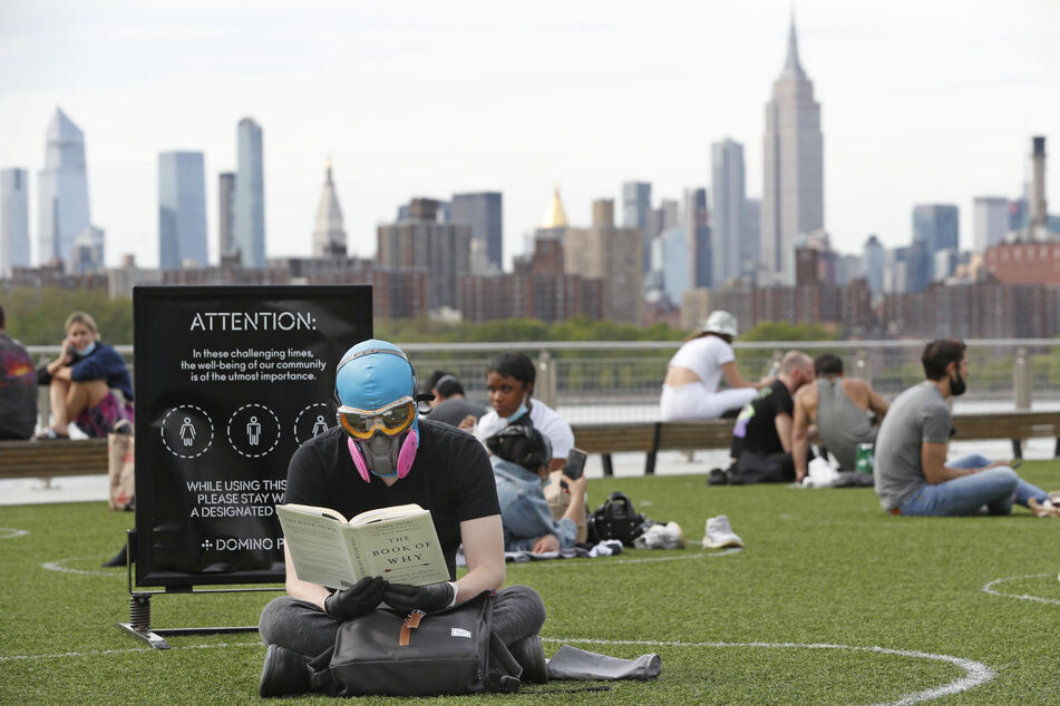 New York: Ein Mann trägt eine Schutzbrille und eine Schutzmaske, während er im Domino Park im Stadtteil Brooklyn und ein Buch liest.