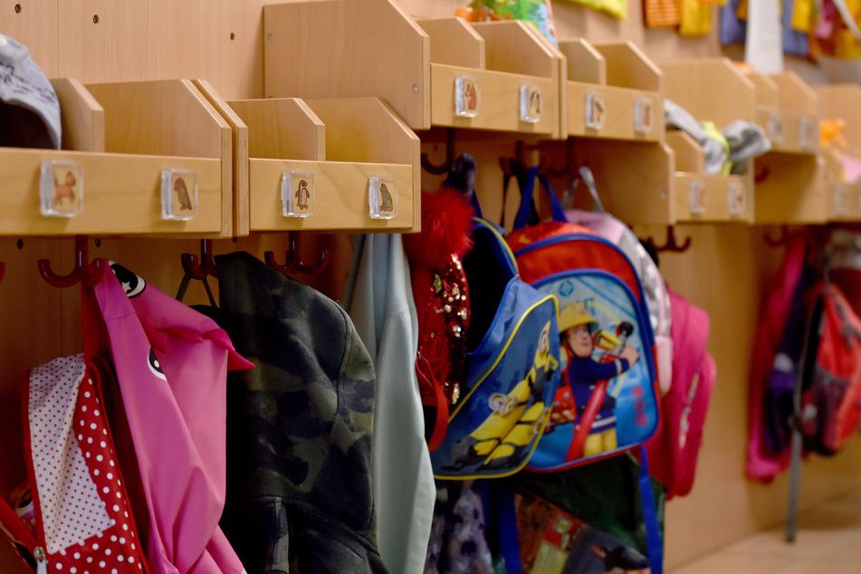 Jacken und Rucksäcke hängen in einer Kita an Haken im Flur.