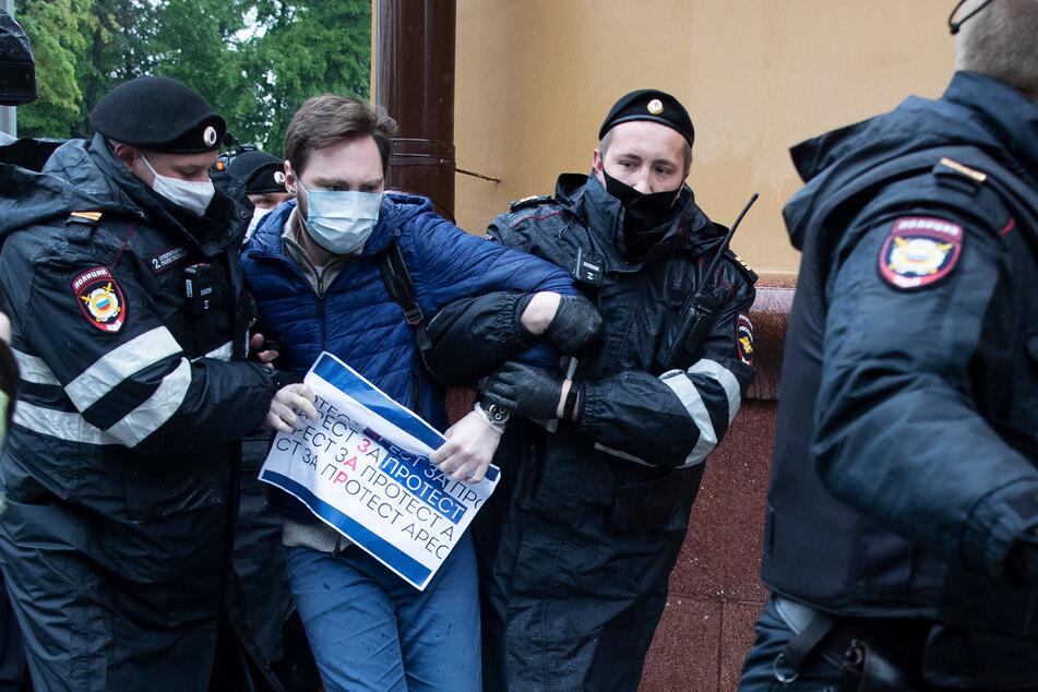 Polizisten halten Kirill Gontscharow fest, nachdem er trotz der Corona-Maßnahmen vor dem Polizeipräsidium der Stadt alleine protestiert hat.