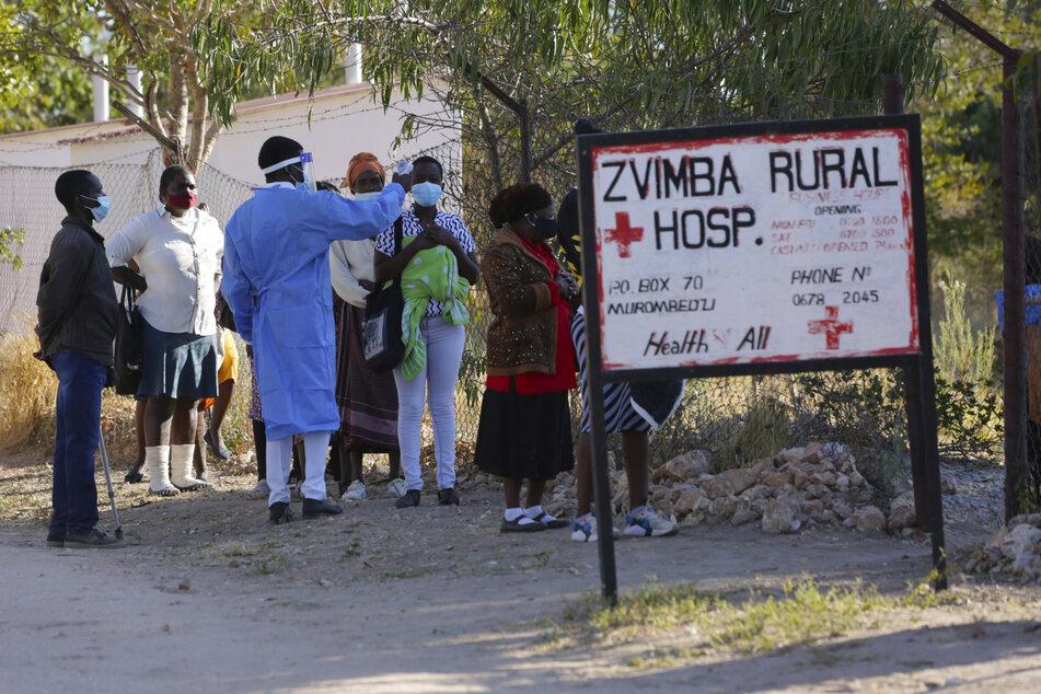 Bewohner lassen ihre Temperatur messen, bevor sie sich im örtlichen Krankenhaus behandeln lassen.