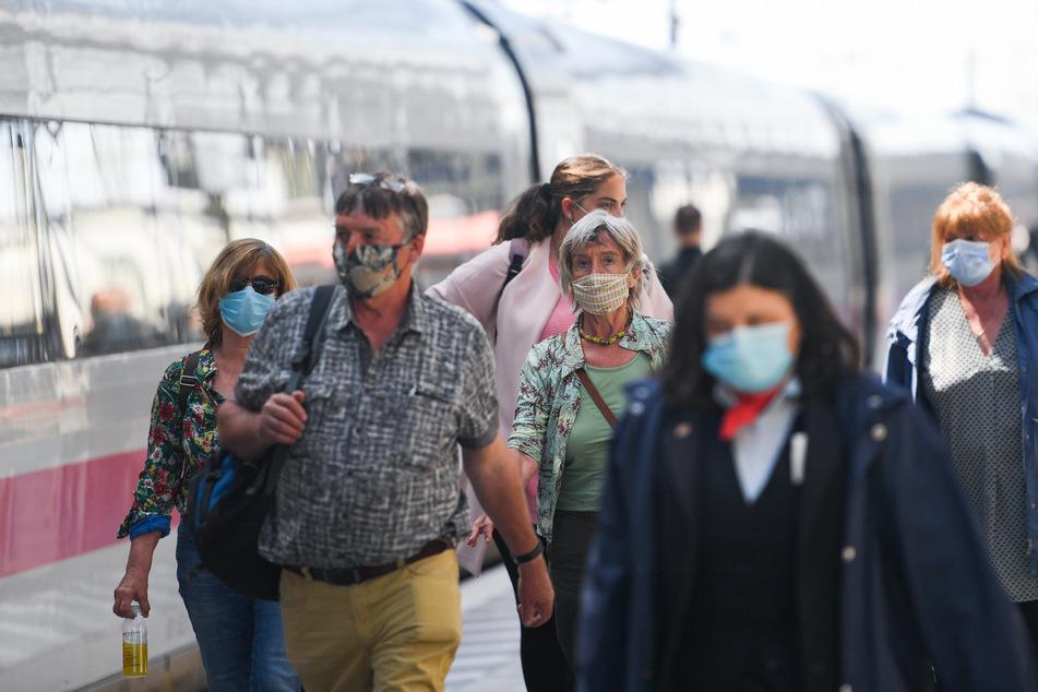 Reisende mit Mundschutzen verlassen einen ICE. (Symbolbild)