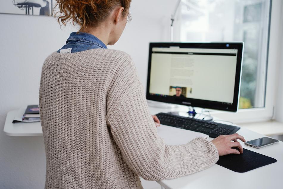 Eine Frau arbeitet in ihrer Wohnung vor einem Computer an einem Stehtisch.