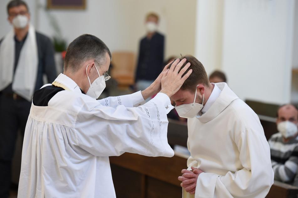 Pfarrvikar Wolfgang Rothe (53, l.) segnet Henry Frömmichen (21) bei einem Gottesdienst.