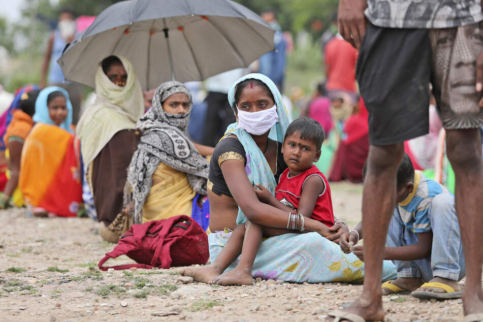 Wanderarbeiter-Familien warten auf die Messung ihrer Körpertemperatur, bevor sie mit dem Zug zurück in ihre Heimatdörfer fahren dürfen.