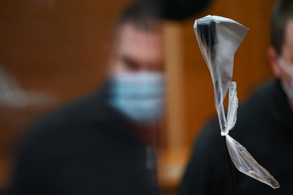 Der Angeklagte spiegelt sich zu Beginn des Mordprozesses im Gerichtssaal des Landgerichts Frankfurt in einer Trennscheibe.