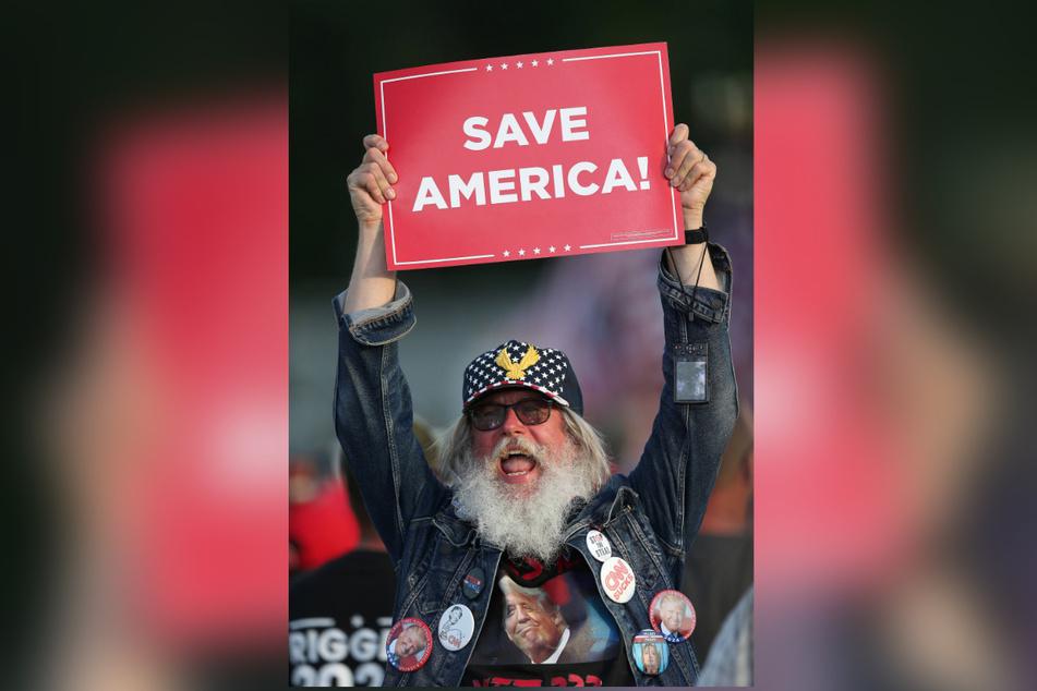 """Die von Trump geworfenen Hüte tragen die Aufschrift """"Save America"""" (""""Rettet Amerika"""")."""