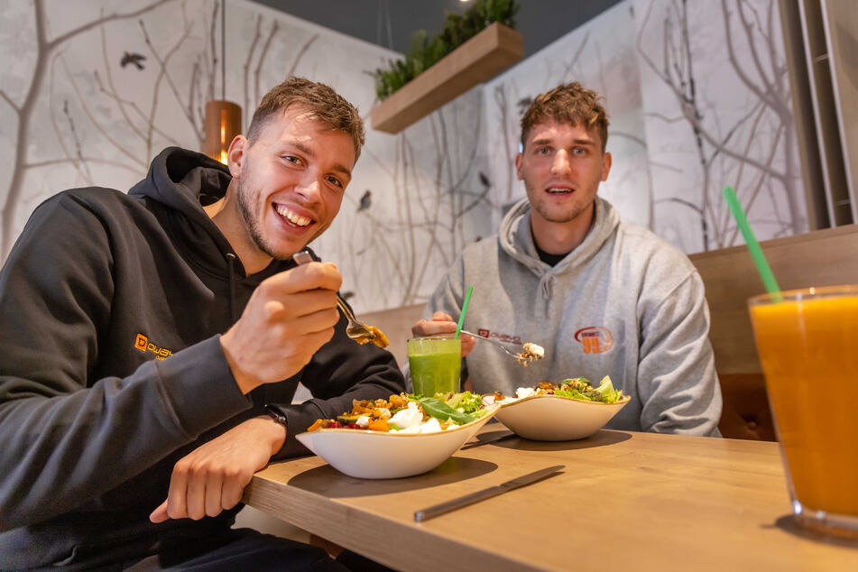 """Die Niners-Basketballer Jan Niklas Wimberg (25, l.) und Jonas Richter (24) schätzen das frische Angebot im """"dean&david""""."""