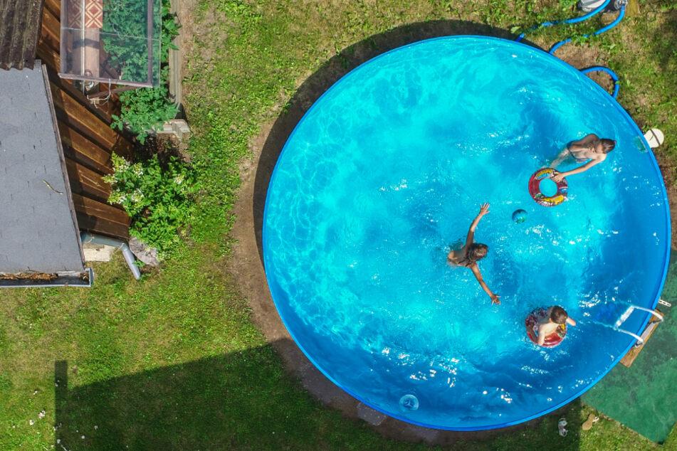 Kinder planschen bei Sommerwetter in einem privaten Pool im Garten. (Symbolbild)