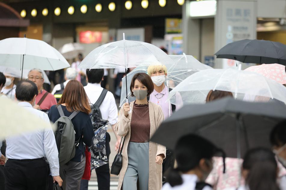 Passanten mit Schutzmasken und Regenschirmen gehen in Tokio über eine Straße.