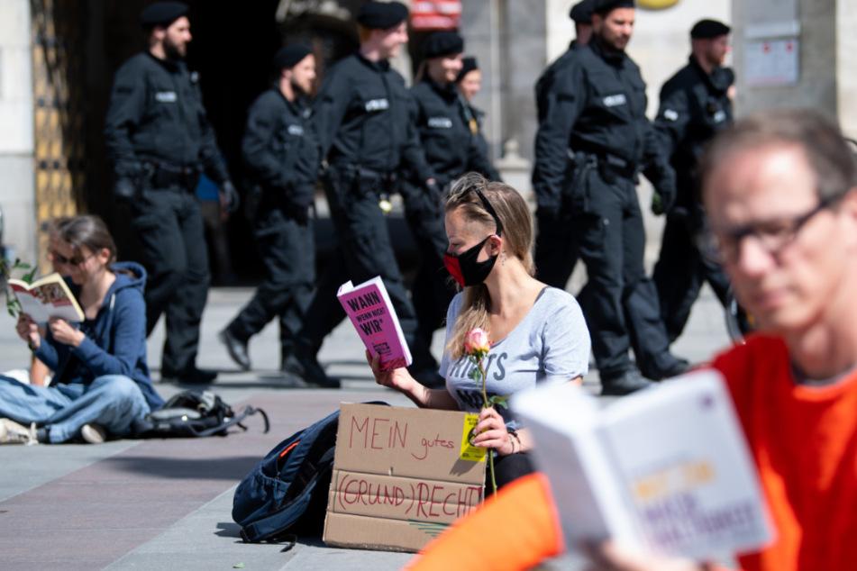 """Teilnehmer der Kundgebung """"Lesen für die Demokratie"""" sitzen auf dem Marienplatz und haben dabei ein Schild mit der Aufschrift """"Mein gutes (Grund)Recht"""" aufgestellt."""