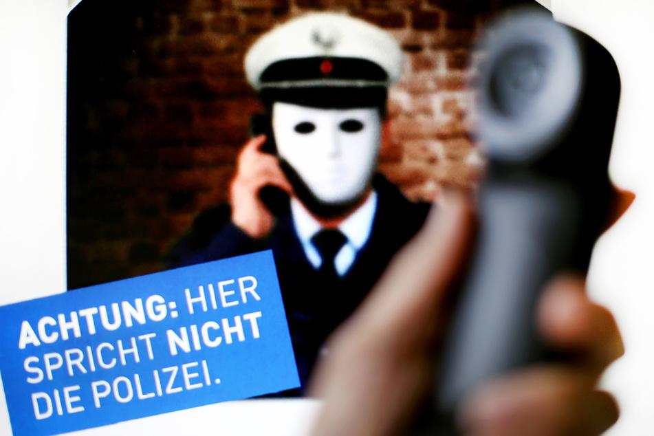 Die Polizei warnt auf einem Plakat vor Trickbetrug am Telefon durch falsche Polizeibeamte.