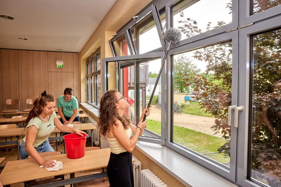 Nina (r.), Tabea und Tim (alle 14) nehmen selbst Staubwedel und Lappen in die Hand, putzen ihr Klassenzimmer.