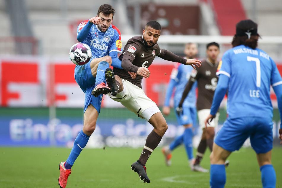 Intensive Partie: FC St. Paulis Daniel-Kofi Kyereh (r.) und Holstein Kiels Jonas Meffert im Zweikampf um den Ball.