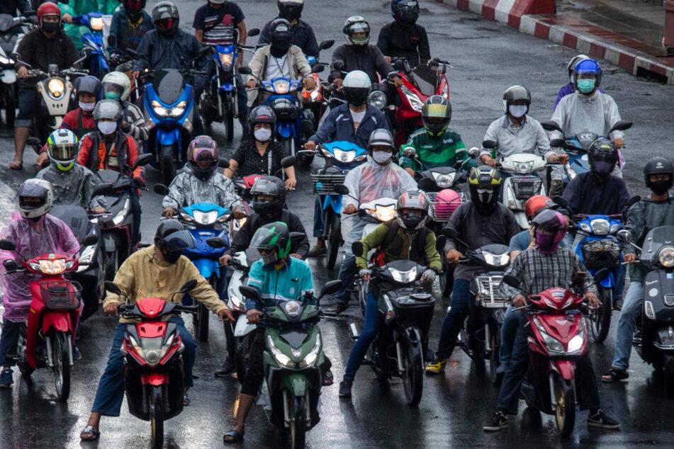 Thailand, Bangkok: Zahlreiche Motorradfahrer, die an einer Ampel stehen, tragen Mundschutze, um die weitere Ausbreitung des Coronavirus zu verhindern.