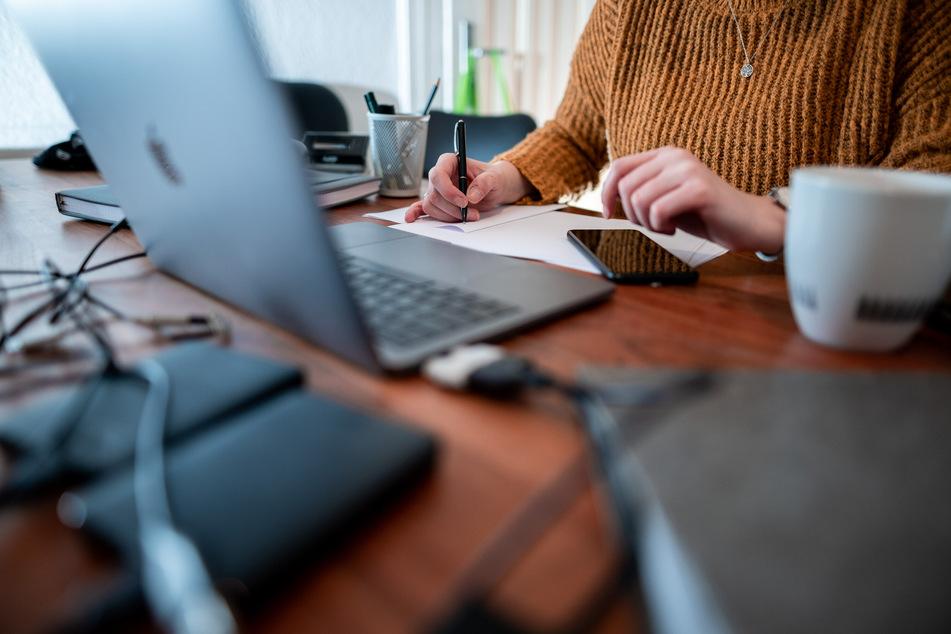 Eine Frau sitzt mit einem Laptop an einem Tisch im Homeoffice. Die Bundesregierung geht mit gutem Beispiel voran.