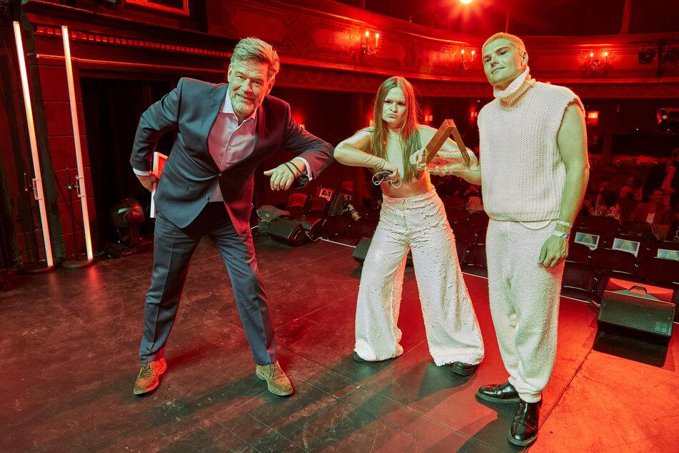 Alexander Schulz (l), Gründer und Geschäftsführer des Reeperbahn-Festivals, und die Gewinner des Anchor-Award, Demian (r) und Inez von der Band Ätna, stehen mit der Trophäe auf der Bühne im St.-Pauli-Theater.