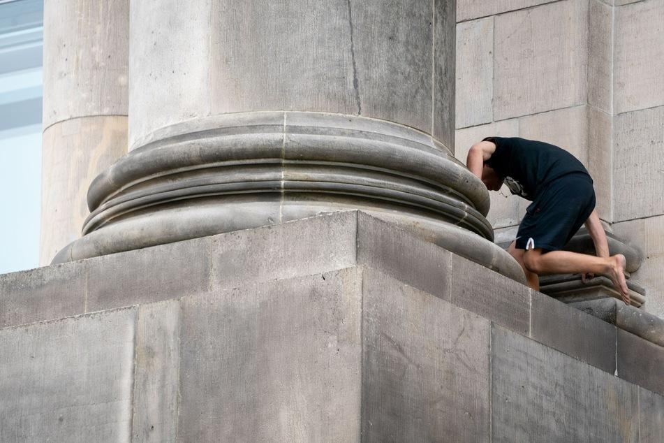 Der barfüßige Mann lief und kletterte eine Zeit lang auf einem Vorsprung im unteren Bereich des Reichstagsgebäudes auf der Spreeseite hin und her.