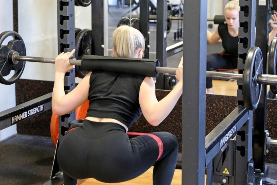 Eine junge Frau trainiert im Fitnessstudio.