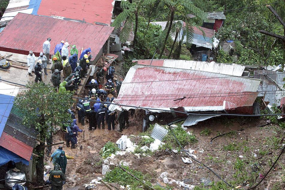 Rettungskräfte suchen nach Opfern in einem Haus, das durch einen Erdrutsch verschüttet wurde.