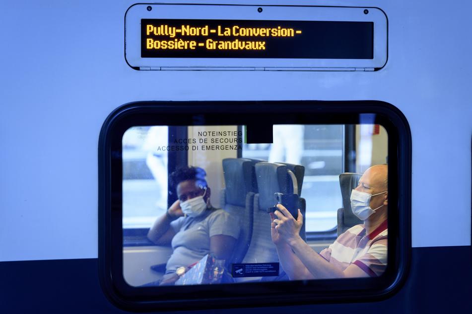 Passagiere sitzen mit Mundschutze in einem Zug der SBB CFF am Bahnhof.