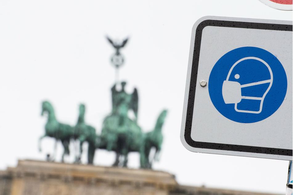 Am Pariser Platz vor dem Brandenburger Tor weist ein Hinweisschild auf die Maskenpflicht hin.