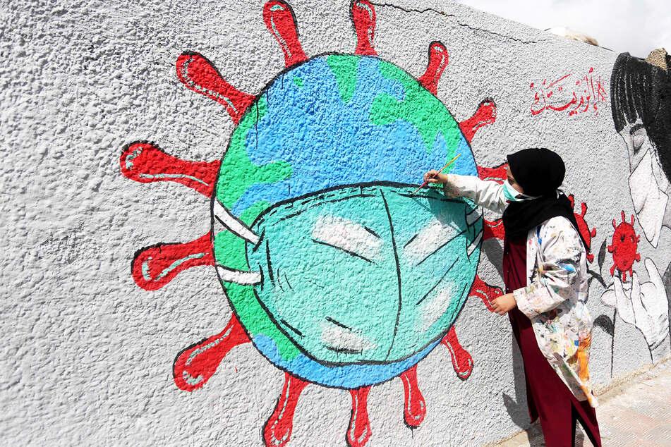Eine Frau malt eine Coronavirus-Erde an eine Graffiti-Wand.