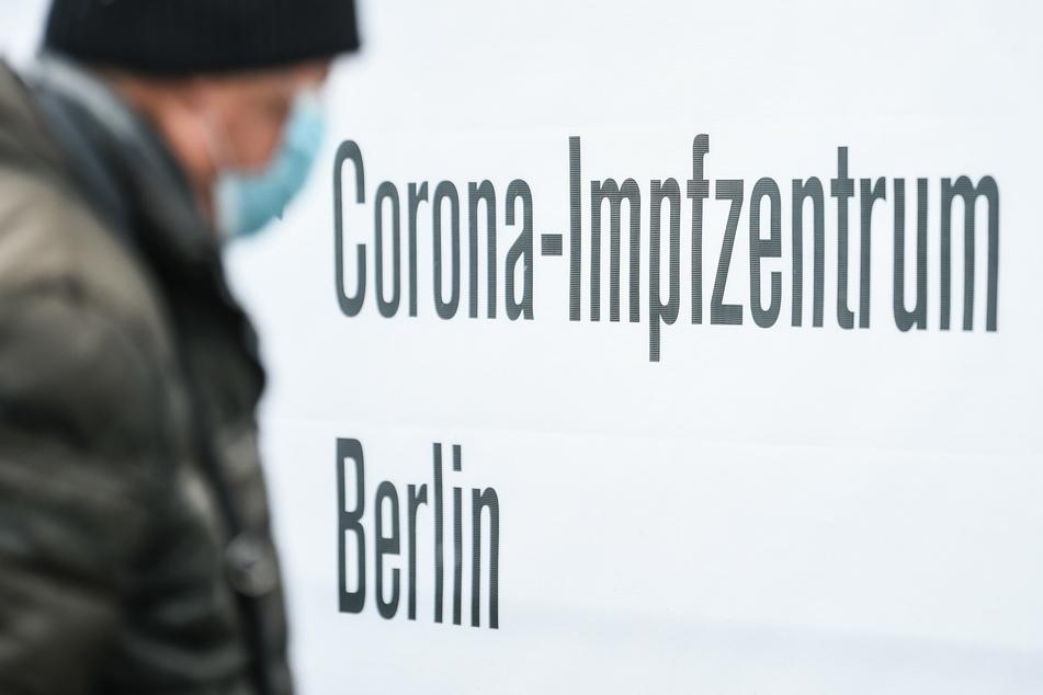 """Eine Person mit Mund-Nasen-Bedeckung geht an einem Schild mit der Aufschrift """"Corona-Impfzentrum Berlin"""" vorbei."""