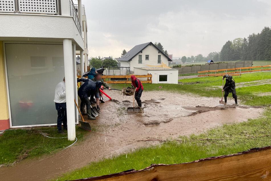 Anwohner des Ortsteils Geyersdorf versuchen ihre Gebäude zu vor den Schlamm- und Wassermassen zu schützen.