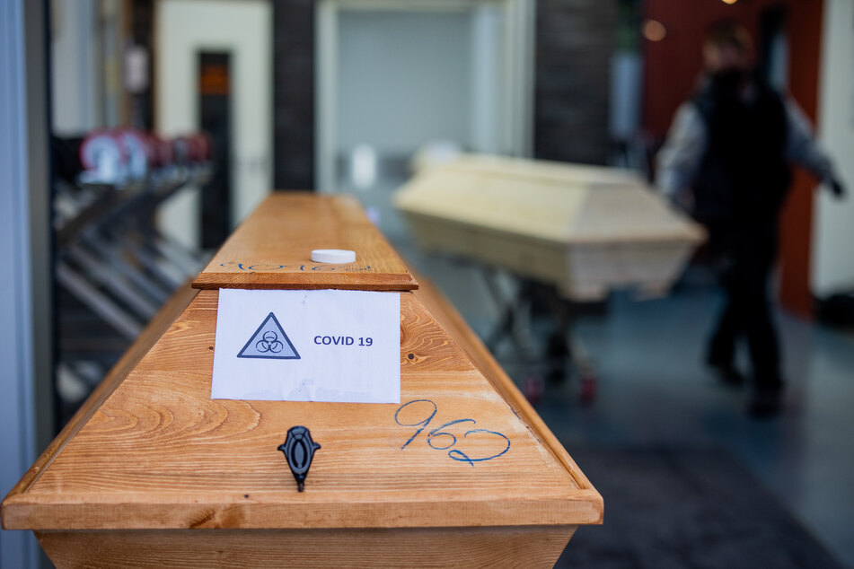 """Ein Sarg mit einem Verstorbenen mit der Aufschrift """"Covid 19"""" wird von einem Bestatter in ein Krematorium eingeliefert."""