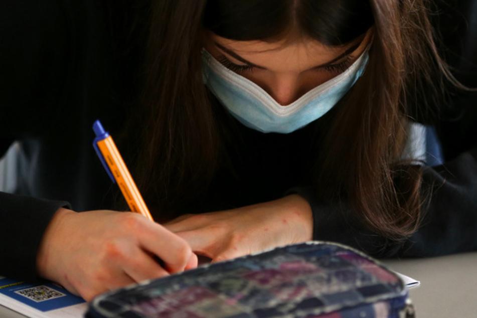 Eine Schülerin sitzt zu Beginn des Unterrichts mit Mundschutz im Klassenzimmer.