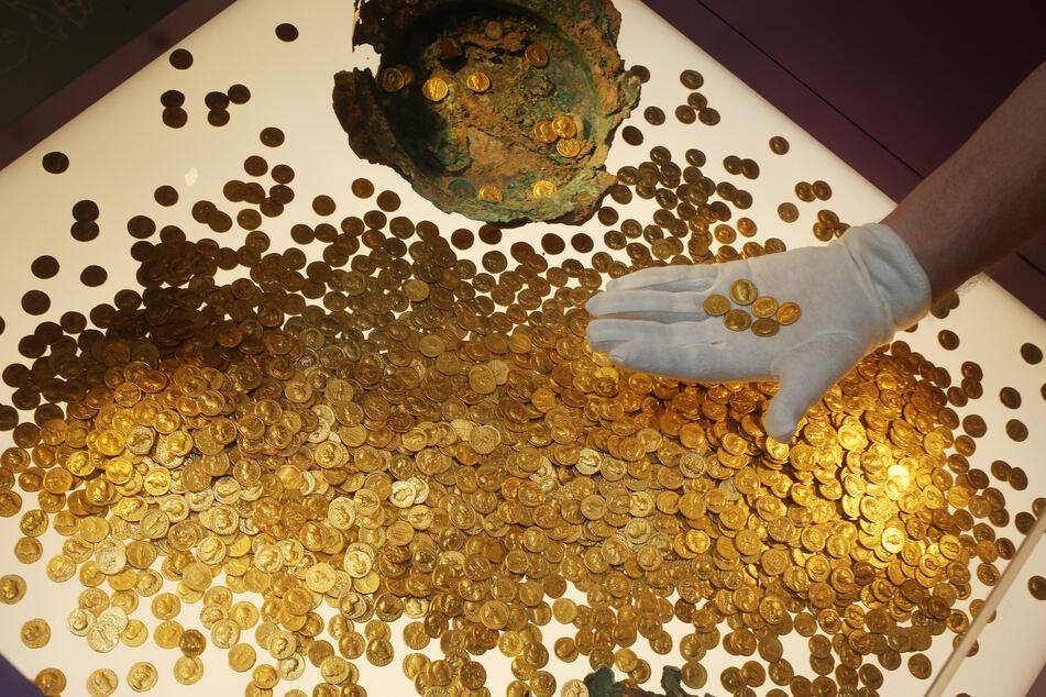 Römische Goldmünzen des Trierer Goldschatzes werden im Rheinischen Landesmuseum Trier in einer Vitrine platziert.