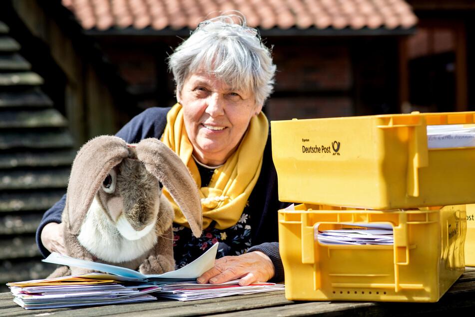 Doris Kröger, Mitarbeiterin des Osterpostamts, sitzt mit einem Osterhasen aus Stoff und vielen Briefen vor dem Gemeindehaus im Ortskern von Ostereistedt.