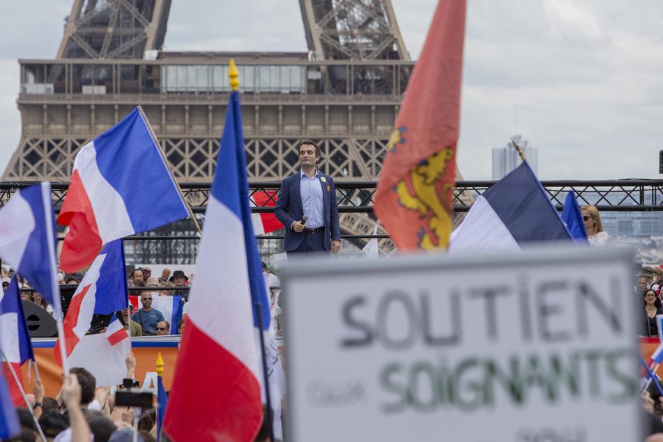 """Frankreich, Paris: Floriant Philippot, Vorsitzender der rechtsextremen Partei """"Les Patriotes"""" spricht auf der """"Droits de l'homme""""-Esplanade am Trocadero-Platz während eines Protests gegen die Impfpflicht für bestimmte Arbeitszweige und den von der Regierung geforderten obligatorischen Impfpass."""