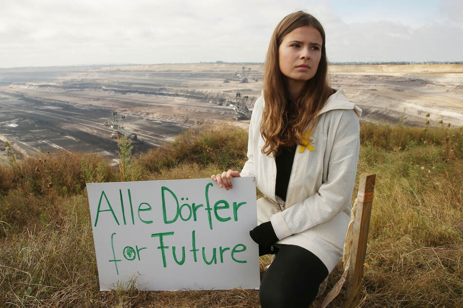 """Die Umweltaktivistin Luisa Neubauer sitzt mit einem Plakat mit der Aufschrift """"Alle Dörfer For Future"""" vor dem Garzweiler Tagebau."""