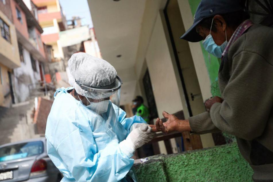 Ein Mann wird im Rahmen einer Haus-zu-Haus-Testkampagne auf das Coronavirus getestet.