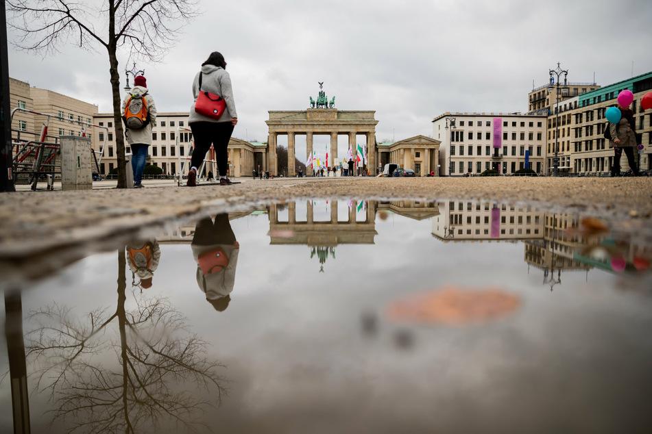 Passanten gehen vor dem Brandenburger Tor, welches sich bei bedecktem Himmel in einer Pfütze spiegelt.