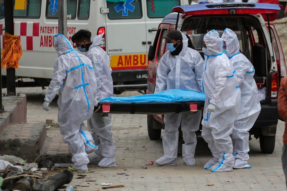 Jammu: Mitarbeiter des Gesundheitswesens und Angehörige tragen den Leichnam einer Person, die an Covid-19 gestorben ist, zur Einäscherung.
