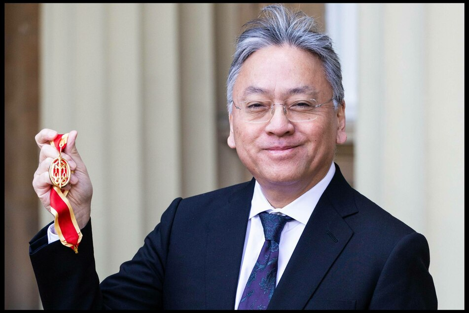 Sir Kazuo Ishiguro poses with his medal after being knighted in 2019 at Buckingham Palace.