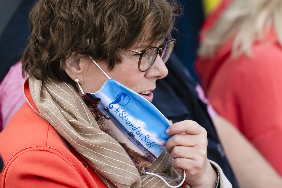 Sabine Sütterlin-Waack (CDU), Innenministerin von Schleswig-Holstein, setzt einen Nasen-Mundschutz auf während des Finales bei den Deutschen Beachvolleyball-Meisterschaften.