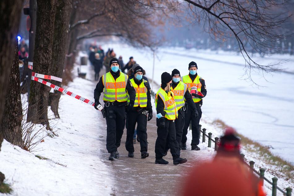 Polizisten räumen und sperren die Eisfläche und die Gehwege am Nymphenburger Kanal in München.