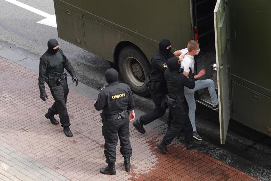 Ein Demonstrant wird von Bereitschaftspolizisten in einen Gefangenentransporter gebracht.