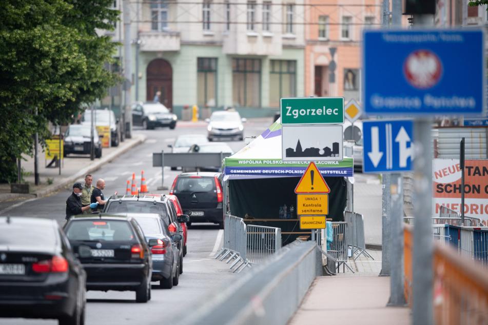 Polnische Grenzpolizisten stehen auf der Brücke der Freundschaft an der polnischen Grenze vor Zgorzelec und kontrollieren mit einem Thermometer die Körpertemperatur der Autofahrer, die aus Görlitz kommend nach Polen einreisen wollen.