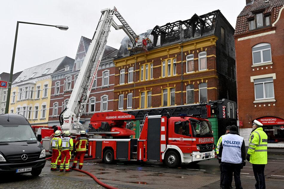 Feuerwehrleute bekämpfen Glutnester nach dem Brand in dem Mehrfamilienhaus.