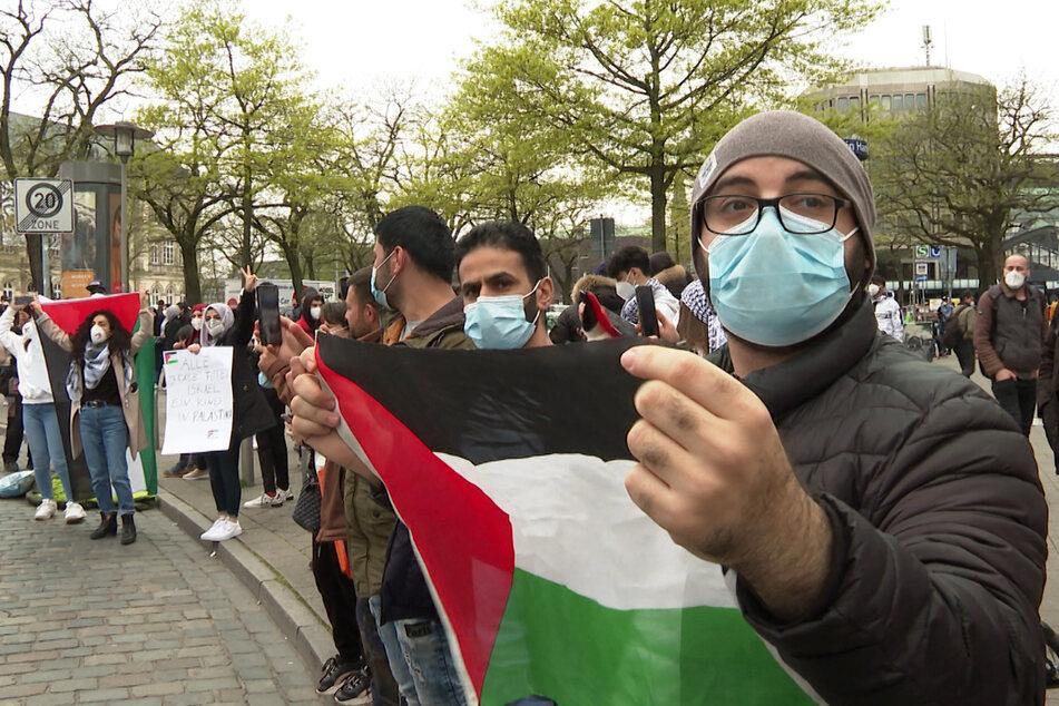 Teilnehmer der Demo halten Flaggen der Palästinensischen Autonomiegebiete.