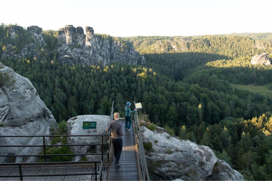 Touristen stehen im Nationalpark Sächsische Schweiz in der Felsenburg Neurathen auf einer Aussichtsplattform.