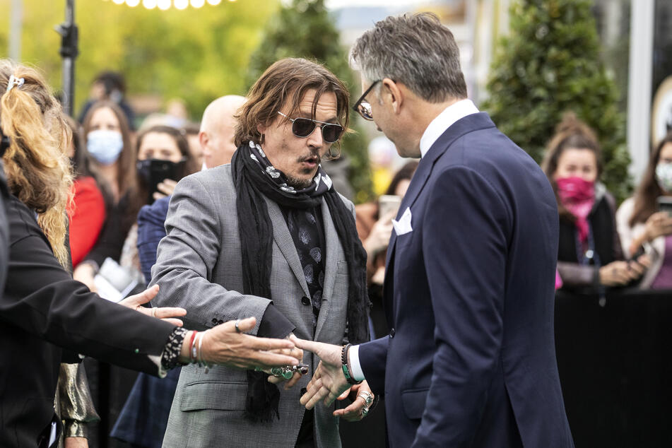 Johnny Depp and Christian Jungen (r.), artistic director of the Zurich Film Festival, greet each other during the 16th Zurich Film Festival.