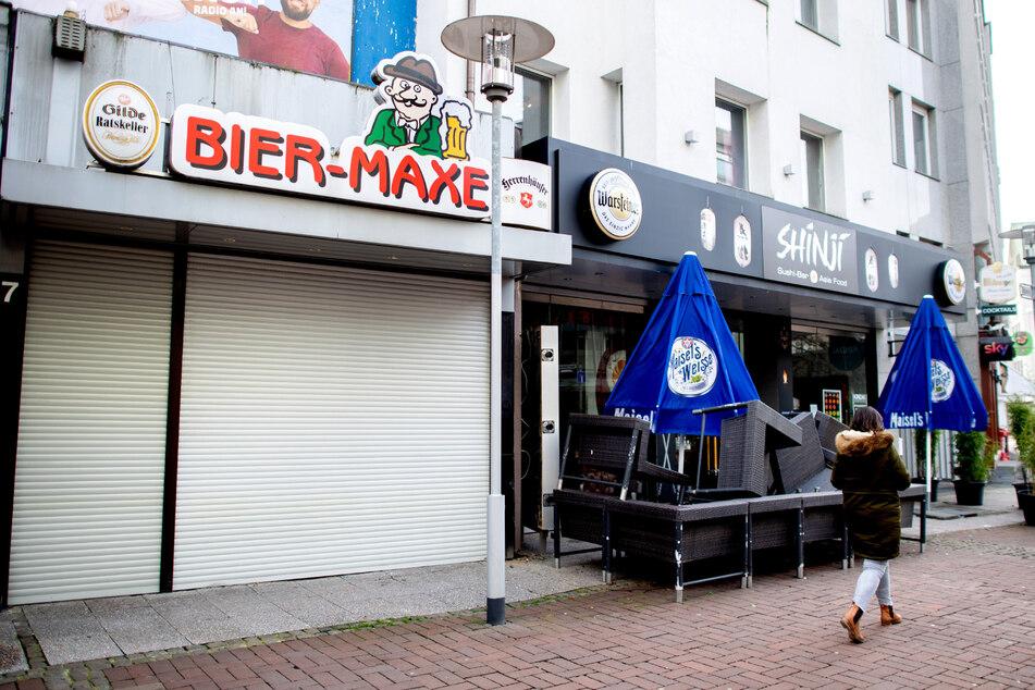 Eine Passantin geht an einer geschlossenen Kneipe und einer Sushi-Bar vorbei. (Symbolbild)