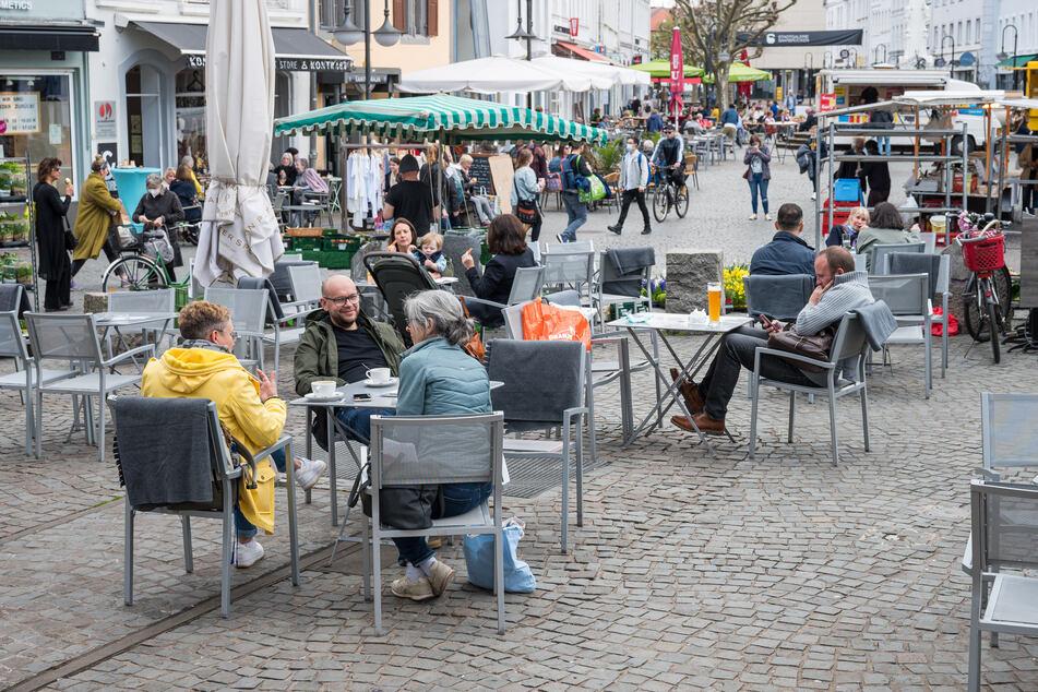 Saarland, Saarbrücken: Auf dem St. Johanner Markt in Saarbrücken sitzen Menschen im Außenbereich von Gastronomiebetrieben.