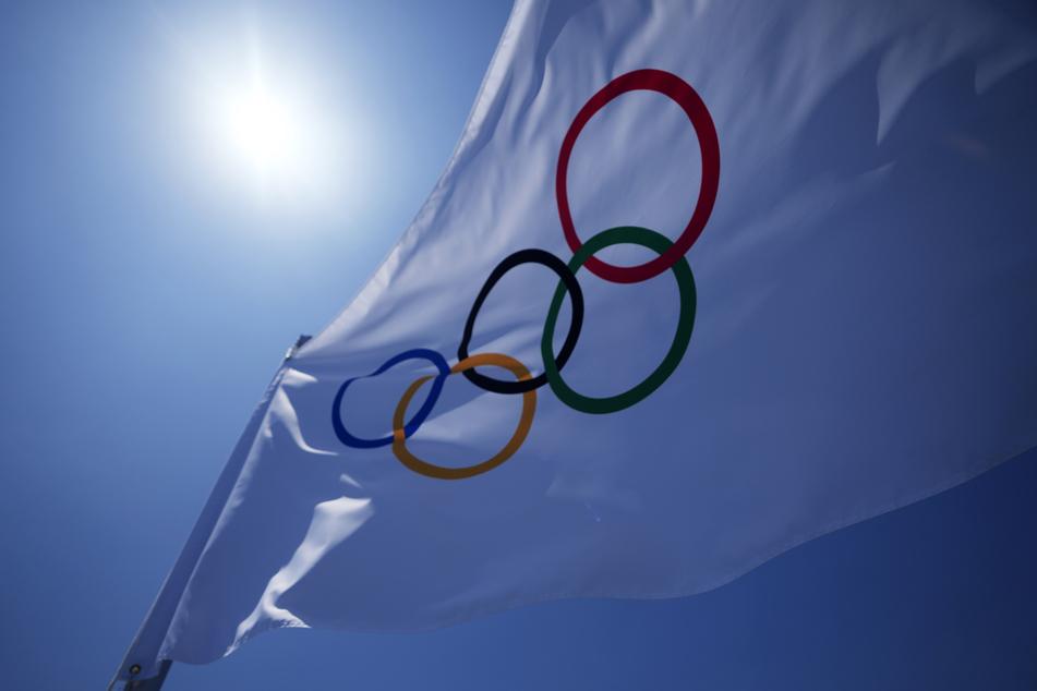 Die olympischen Ringe auf einer Flagge vor dem Stadion. Die Spiele beginnen am Freitag, dem 23. Juli.
