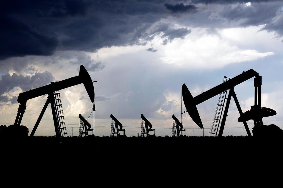Dunkle Wolken ziehen direkt hinter einer Reihe von Tiefpumpen in einem Ölfeld in Texas vorbei.